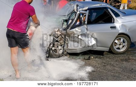 Man extinguishes the car with a fire extinguisher. Damaged vehicle closeup after car crash.