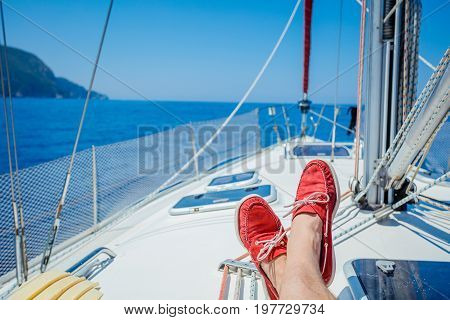 A pair of man legs in red topsiders on white yacht deck. Yachting