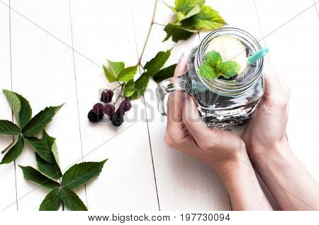 Summer drink with blackberries, lemon and mint in female hands on a white rustic wooden background with a copy space top view.