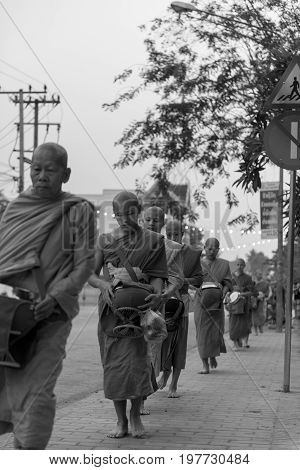 LUANG PRABANG LAOS - MARCH 12 2017: Black and white and vertical picture of many monks going in line to Buddhist Alms Giving Ceremony where local people offers food and money before the sunrise in Luang Prabang Laos.