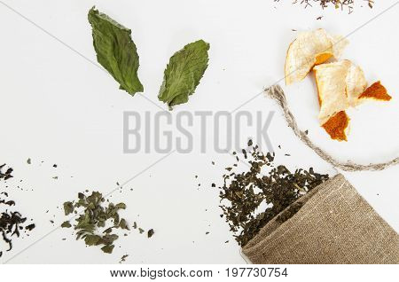 Mint and melissa leafs green and black tea dried orange peel linen bag with empty space on white background. Top view.