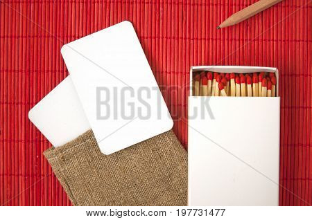 Mock up of white paper cards in linen bag and matchbox on red background.