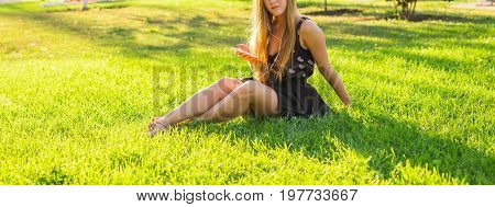Young beautiful woman enjoying music outdoors on headphones lying on grass and looking happy