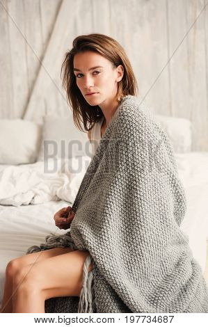 young sexy woman relaxing at home in bed in weekend morning wrapped in knitted blanket. Casual lifestyle
