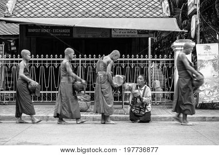 LUANG PRABANG LAOS - MARCH 12 2017: Black and white picture of Lao woman on her knees giving to the monks food and money for the Buddhist Alms Giving Ceremony before the sunrise in Luang Prabang Laos.