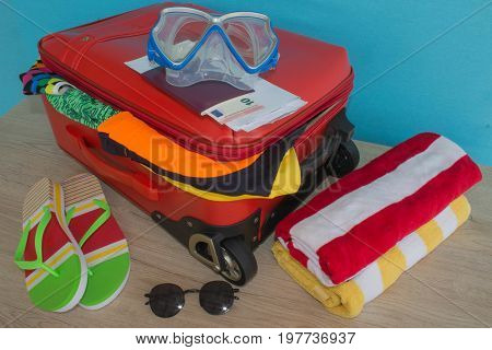 Suitcase with things for spending summer vacation things prepared for travel. Red suitcase with different things
