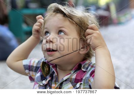 Child puts on amulet in summer park