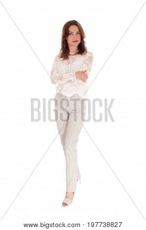A beautiful young woman in a lace blouse and brunette hair standing in dress pants with arms crossed isolated for white background