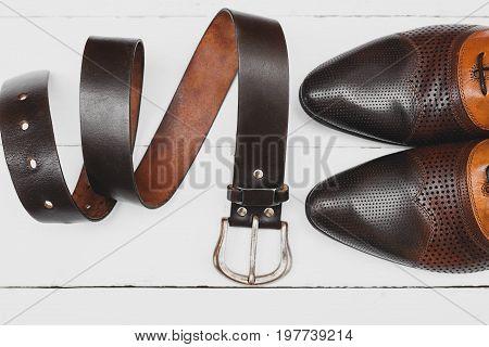 Stylish men's shoes and belt on white background