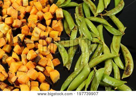 Roasted snap beans and cubed yams sprinkled with olive oil on baking pan