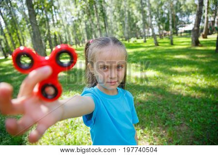 little girl with spinner in her hands close up