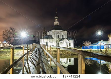 Suzdal, Russia. wooden bridge through the Kamenka River to Church of Epiphany and Nativity Cathedral of Suzdal Kremlin at night in summer