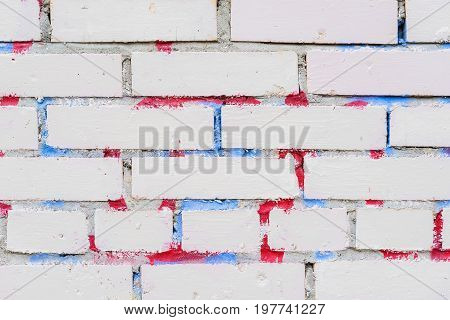 Texture of grungy dirty white brick wall. With the remnants of paint and stains from graffiti. Cute background on modern urban themes