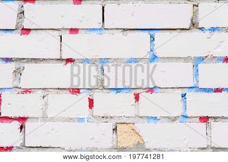 Beautiful abstract background from grungy dirty white brick wall. With the remnants of paint and stains from graffiti. Urban background with space for text. Exposed brick on damaged wall