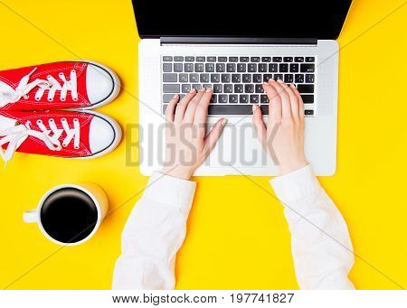 Hands Typing On Laptop Near Cup Of Coffee And Gumshoes