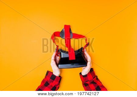 Female hands holding VR glasses on yellow background