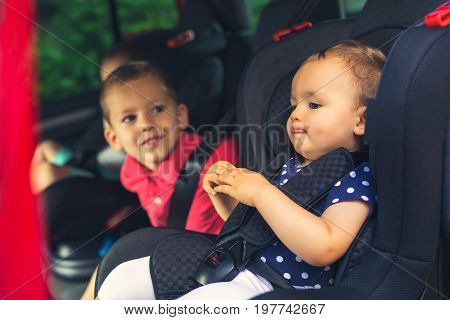 Three children in car safety seat - family transport safety road trip and people concept