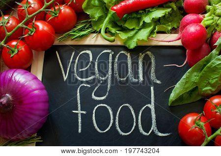 Vegan food chalk inscription Salad, radish, Onion, corn, tomatoes, garlic, carrots, cucumber, pepper, eggplant, basil rosemary around inscription Top view Diet and healthy concept Close up