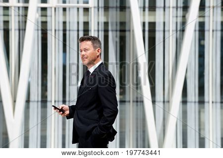 Portrait Of Businessman Thinking And Holding Mobile Phone