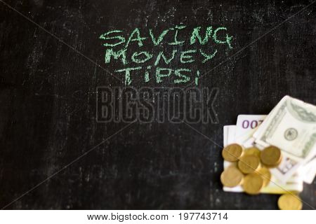 saving money tips inscription on chalk board and blurred money.
