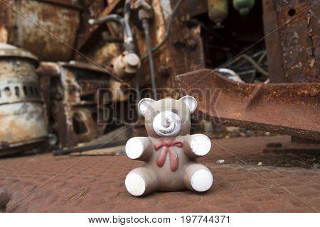 Close uo of teddy bear plastic toy in rusting heavy equipment in junkyard