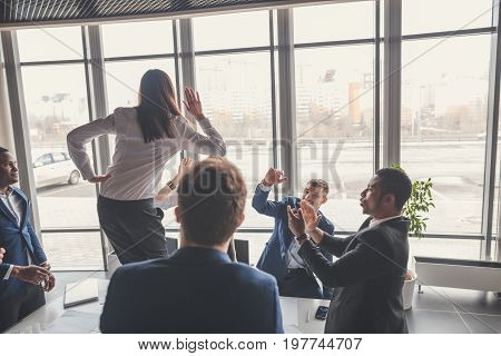 High-five. cheerful young business people giving high-five while their colleagues looking at them and smiling