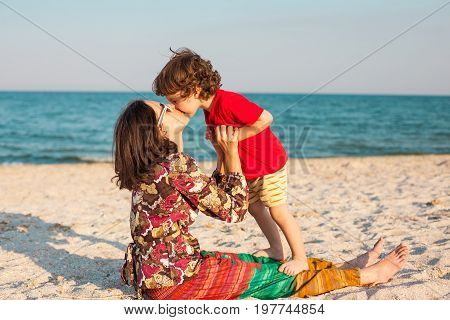 Mother Plays With Her Baby On The Beach.