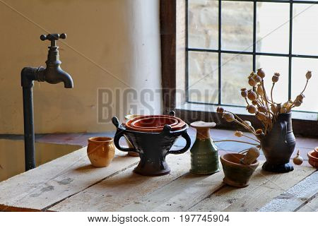 Old Fashioned Brass Standpipe Water Tap Or Fawcett, Over A Wooden Bench With Antique Tudor Style Pot