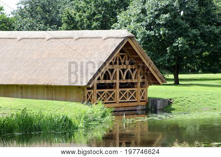 Pretty Tudor Style Wooden Framed Thatch Boathouse In A Wood On The Edge Of A Lake Or River On A Sunn