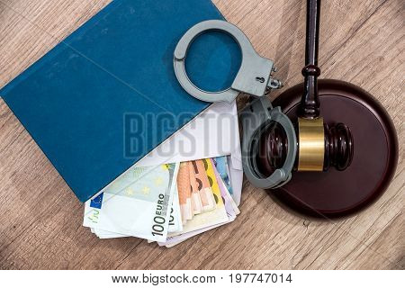 The Concept Of Corruption - Euro Banknotes In An Envelope, Handcuffs And Hammer Judges