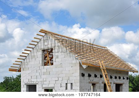 The process of building a private house of cellular concrete blocks and installing a wooden roof truss system.