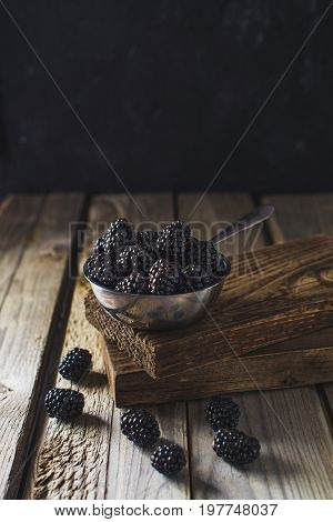 Ripe blackberries in a metalic bowl over wooden background close up. Rustic style