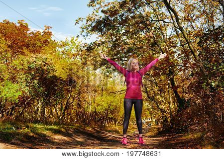 Full photo of young sportswoman preparing for training in autumn park