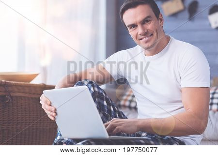 Keep smiling. Handsome male person keeping laptop on the legs while working at home, looking straight at camera