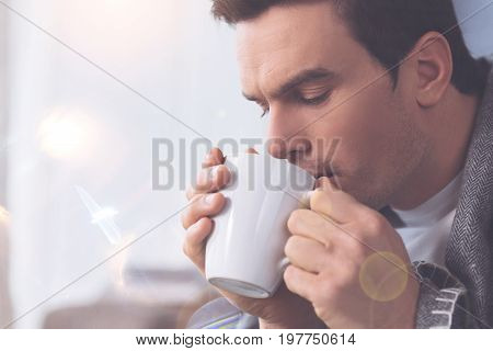 Stay at home. Frustrated man wrinkling his forehead looking downwards into cup while warming himself with tea
