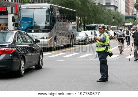 New York July 27 2017: African American police woman is directing traffic during the day in Manhattan.