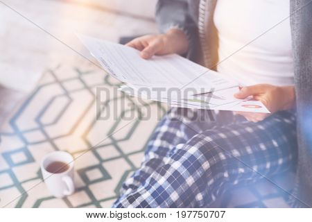Lets work. Male person wearing home clothes sitting on the floor while examining documents