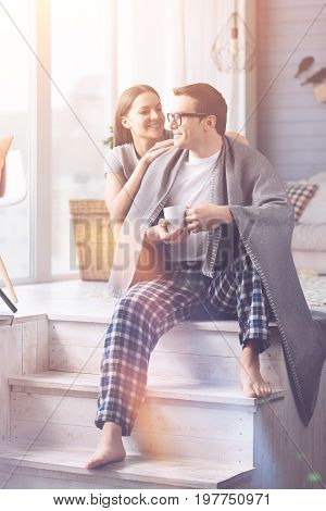 Look at me. Smiling man keeping white cup in both hands looking at window while being in bedroom near his girlfriend