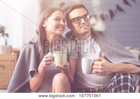 Positive thoughts. Happy young people putting plaid on their shoulders looking forward, smiling man embracing his girlfriend