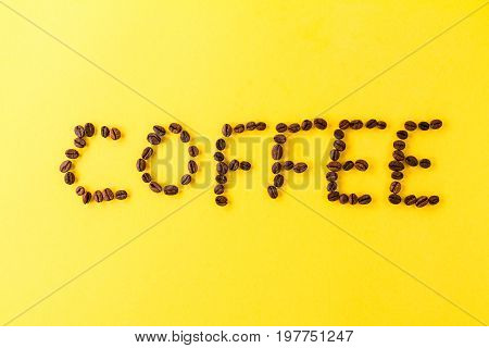 Letters Coffee Beans on yellow vibrant background. Minimalism Food Morning Energy Concept.