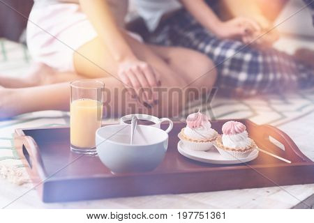 Enjoy your meal. Couple of sweethearts sitting on the bed holding hands together going to have romantic breakfast