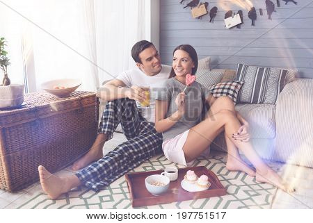 Eat it. Happy man turning his head to pretty girl holding glass with juice in right hand leaning arm on the knee