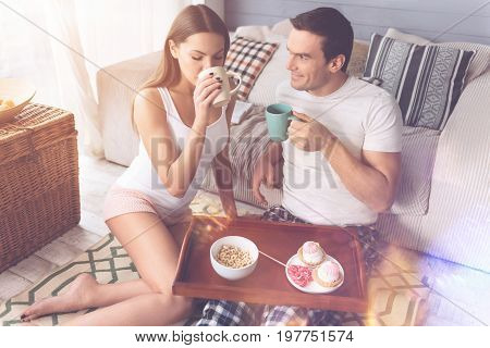 Falling in love. Positive handsome male person leaning his elbow on the sofa holding cup in left hand keeping tray with sweets on the knees
