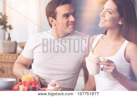 What would you like. Being in love man keeping smile on his face putting right hand on the tray while turning his head to his girl