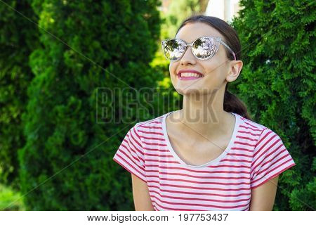 Beautiful girl in pink sun glasses over park background