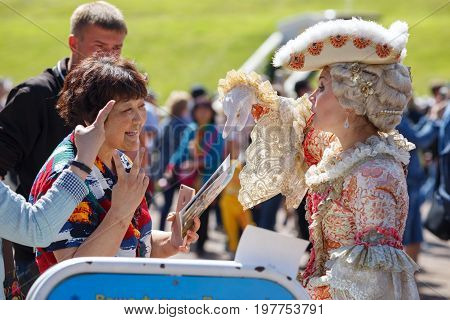 PETERHOF/ RUSSIA - JULY1, 2017. Asian tourists want to be photographed with the model in an ancient court costume in the Peterhof park. Saint Peterbug, Russia.