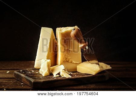 Parmesan cheese on wooden board. Pieces of cheese parmesan on wooden table and cheese knife. Vintage view.