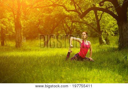 Yoga training outside. Girl practicing yoga in garden, one-legged king pigeon pose. yoga asana Eka Pada Rajakapotasana. Toned image.