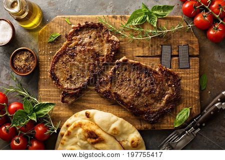 Grilled ribeye steaks with herbs and spices on a wooden board