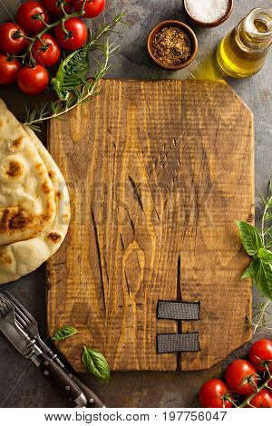 Food background with cutting board, tomatoes, oil and bread, copyspace overhead shot